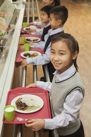 school canteen: Los escolares de pie en línea en la cafetería de la escuela Foto de archivo