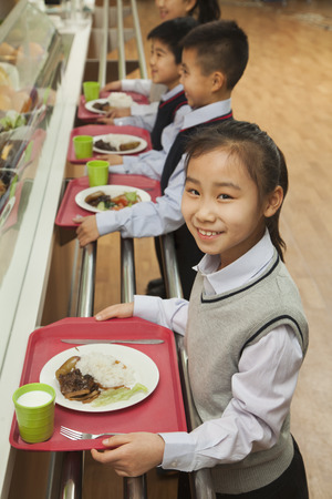 School children standing in line in school cafeteria photo