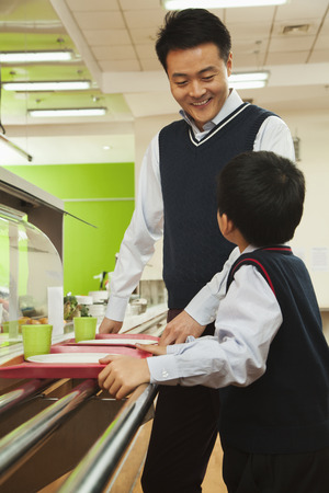school cafeteria: Teacher and student talking in school cafeteria Stock Photo