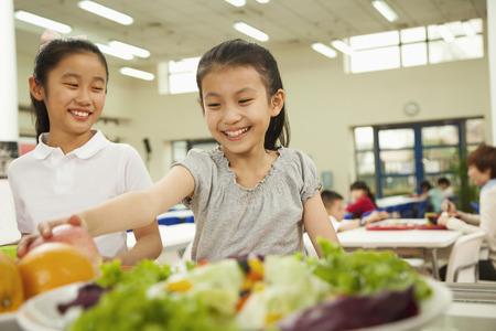 Die Schüler erreichen für gesundes Essen in Schulkantine Lizenzfreie Bilder