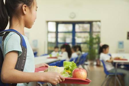 niño escuela: Muchacha de la escuela que sostiene la bandeja de comida en la cafetería de la escuela