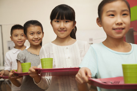 school cafeteria: Row of students standing in line in school cafeteria Stock Photo