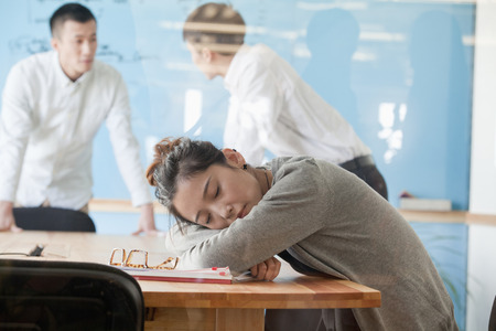 Young businesswoman sleeping during meeting photo