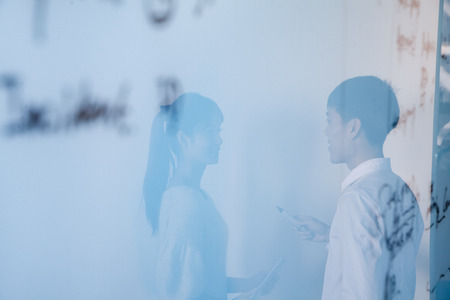 Reflection of businessman and businesswoman talking in the office