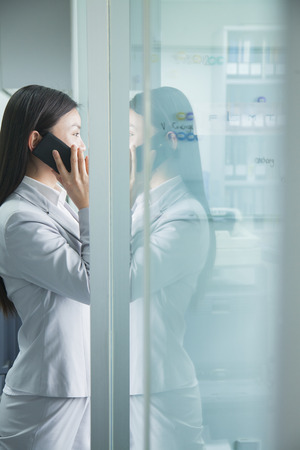 Businesswoman On Phone Reflected in Glass photo