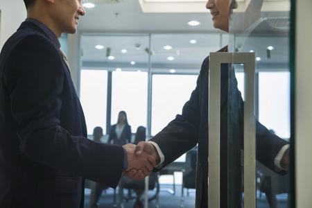 abriendo puerta: Empresarios estrechar la mano Foto de archivo