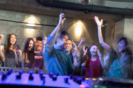 night club series: A view from DJs deck of a crowd dancing in nightclub,