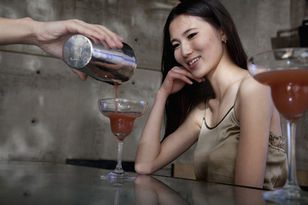 night club series: Bartender serving a cocktail to a young woman