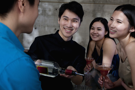 night club series: A young men bartender serving drinks to group of friends