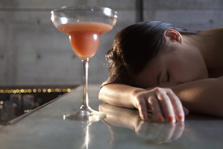 alcohol drinks: Young woman passed out on bar counter