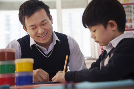 some under 18: Teacher helping schoolboy with arts and crafts, Beijing Stock Photo