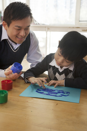 some under 18: Teacher and student finger painting in art class