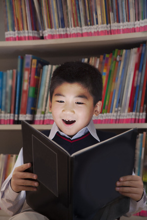 Schoolboy reading a book with her face lit up  photo