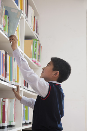 Schoolboy reaching for book off bookshelf photo