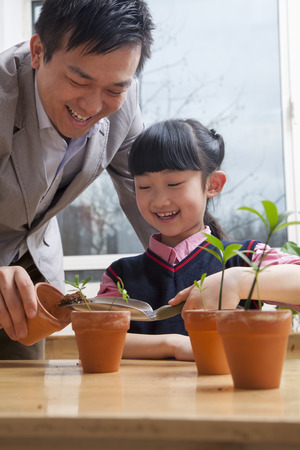 some under 18: Teacher and schoolgirl planting plants into flower pots