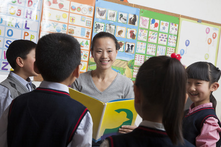 some under 18: Teacher reading to her elementary school students Stock Photo