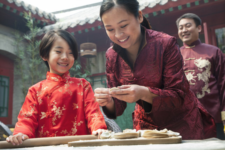 traditional culture: Mother and daughter making dumplings in traditional clothing