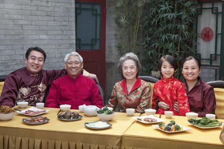 ni�os chinos: Retrato de familia disfrutando de comida china en la ropa tradicional china