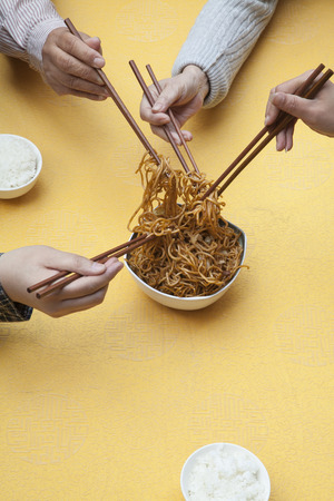 Close up of people holding chopsticks and sharing one dish
