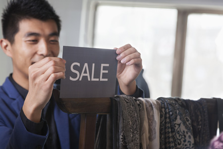 above 21: Store clerk putting up for sale sign at fashion store Stock Photo