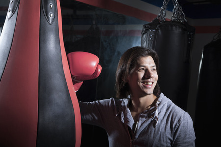 above 30: Portrait of smiling young man at the boxing gym leaning on punching bag