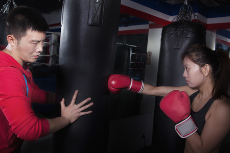 punching bag: Boxing couch holding the punching bag and training a female student Stock Photo