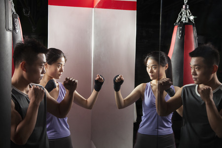 Boxing Instructor and female student practicing stance in front of the mirror at the boxing gym Stock Photo