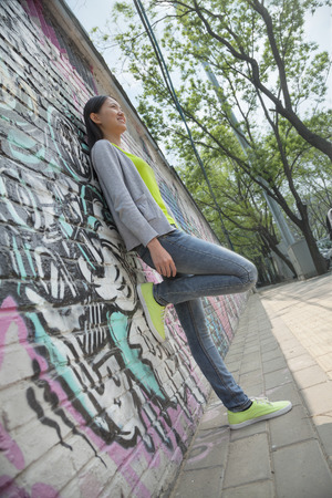 above 18: Young woman leaning and hanging out by a wall covered in graffiti
