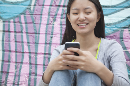 hugging knees: Young smiling woman sitting against a wall with graffiti and looking down and texting on her phone Stock Photo