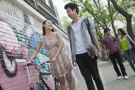 Two young couples walking down the street by a wall with graffiti, smiling and flirting with each other photo