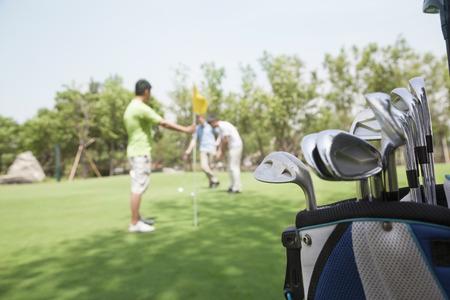Drei Freunde spielen Golf auf dem Golfplatz, den Schwerpunkt auf den Caddy Lizenzfreie Bilder