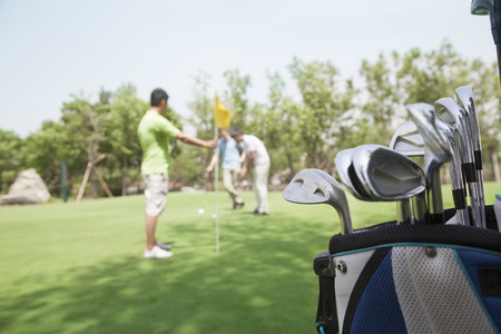 Three friends playing golf on the golf course, focus on the  caddy photo