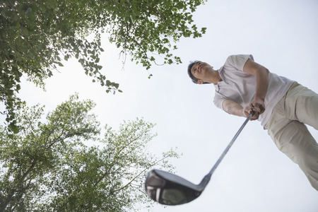 ゴルフ場のゴルフ ・ ボールをヒットする準備男のローアングル ビュー 写真素材