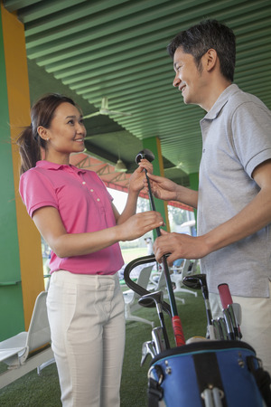 Couple talking and flirting on the golf course, holding a golf club photo