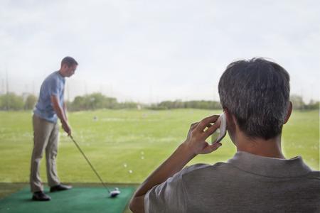 別の男がバック グラウンドでゴルフを再生中に電話の男の背面図