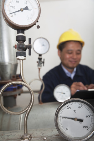 above 30: Close- up on gas gauges with worker in the background in a gas plant, Beijing, China  Stock Photo
