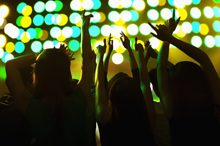 show of hands: Audience watching a rock show, hands in the air, rear view, stage lights Stock Photo
