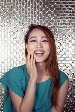 above 18: Portrait of smiling young woman with hand on her face with shiny background