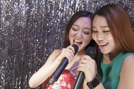 above 18: Two friends holding microphones and singing together at karaoke
