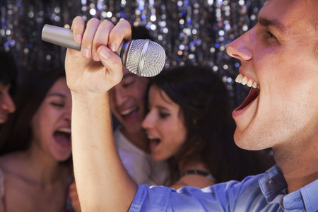 above 21: Close- up of young man holding a microphone and singing at karaoke, friends singing in the background Stock Photo
