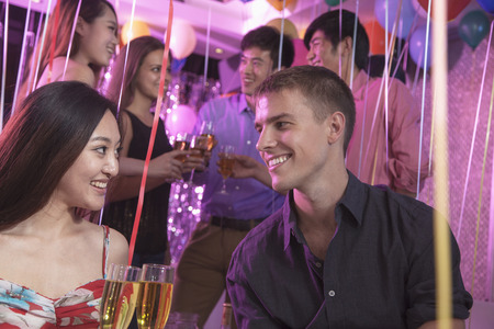 above 18: Group of friends celebrating, toasting with champagne, nightclub in Beijing