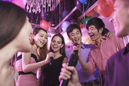Group of friends holding microphones in a nightclub and singing together karaoke Stock Photo