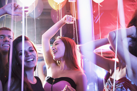 above 18: Multi-ethnic group of friends with hands in the air dancing among balloons in a nightclub