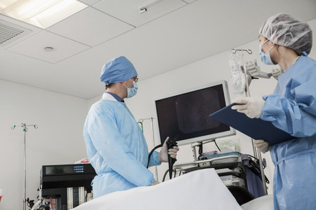 Two surgeons preparing for surgery, patient lying down Stock Photo
