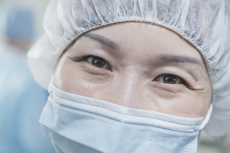 surgical cap: Portrait of surgeon with surgical mask and surgical cap in the operating room