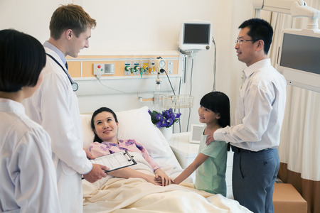 Family visiting the mother in the hospital, discussing with the doctor