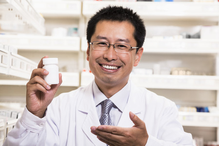 above 30: Portrait of smiling pharmacist holding a prescription medication bottle in his hand Stock Photo
