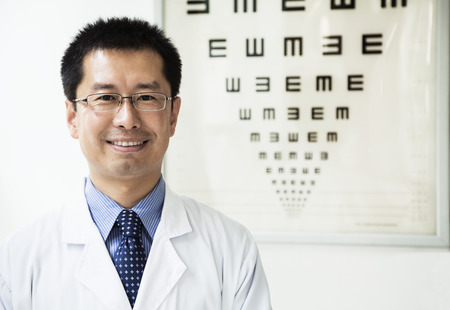 eye chart: Portrait of smiling optometrist with an eye chart in the background