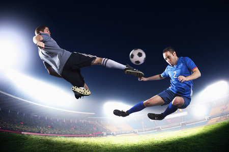 Two soccer players in mid air kicking the soccer ball, stadium lights at night in background photo