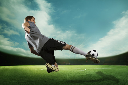soccer sport: Soccer player kicking the soccer ball in mid air, in the stadium with the sky